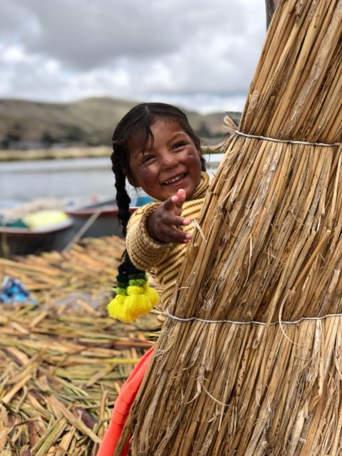 Little Girl on Straw Island hiding behind straw
