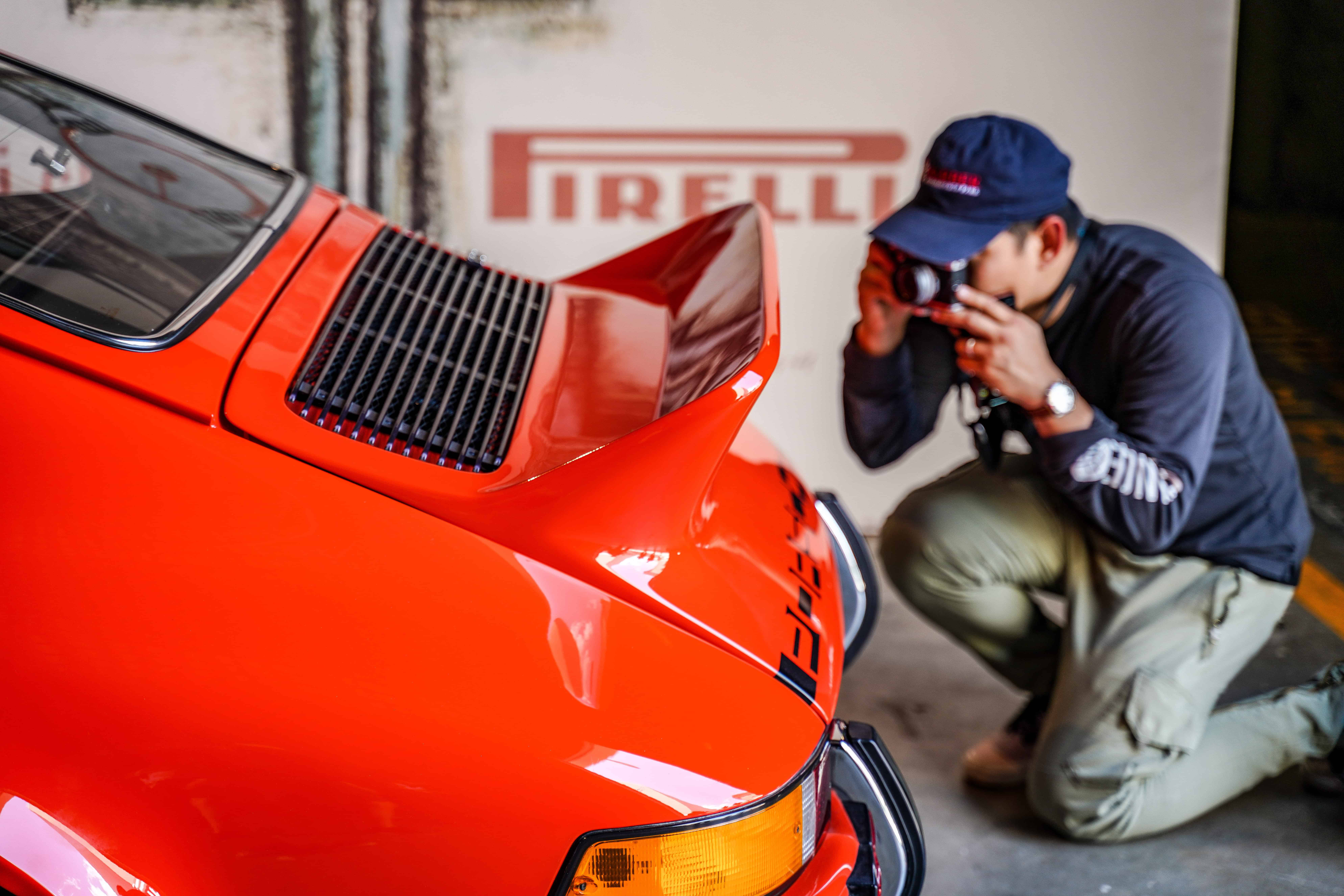 Guy taking picture of orange porsche with camera